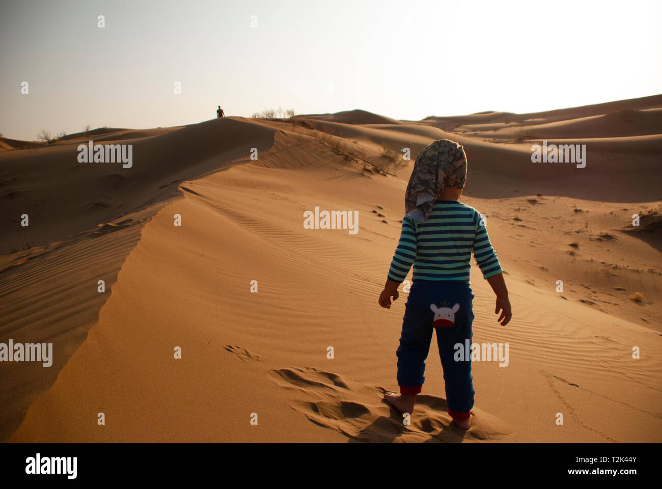 A great shot a colorful dress walikng away to daddy walking on sands sun shines - Stock Image