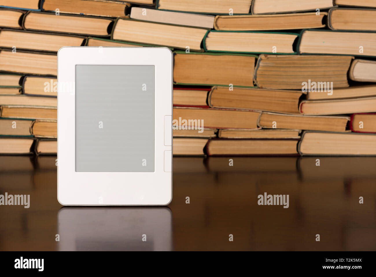 Electronic book on background of regular old books - Stock Image