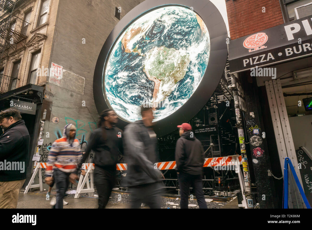 Visitors pass a livestream view of the planet Earth taken from a  NASA satellite is projected on an installation entitled 'blu Marble' on Ludlow Street in the Lower East Side neighborhood of New York on Sunday, March 31, 2019. The work by artist Sebastian Errazuriz is sponsored by the vaping company blu as part of their charitable 'Pledge World by blu' campaign. (© Richard B. Levine) - Stock Image