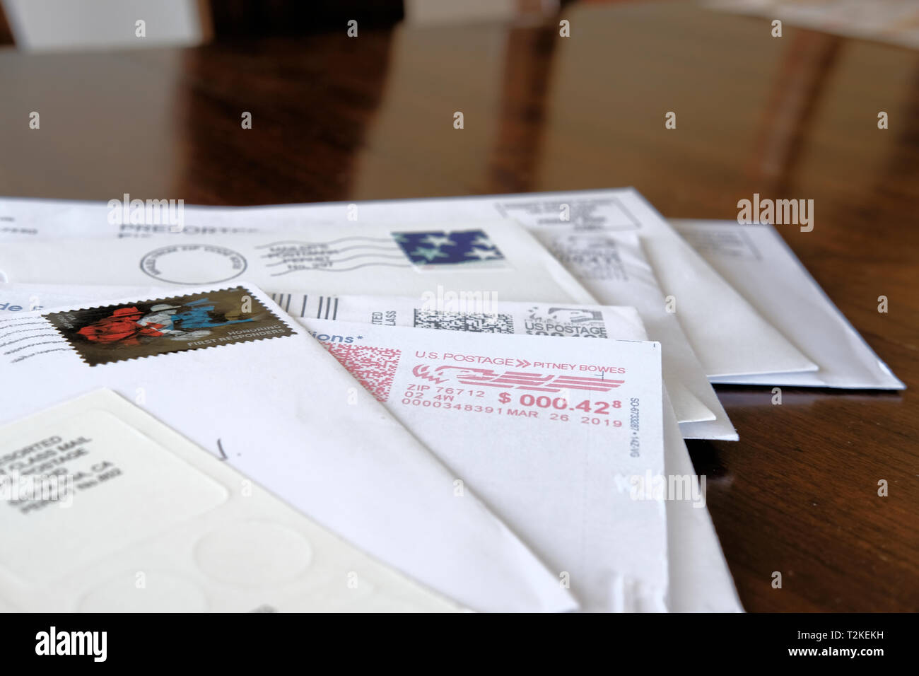 Assorted envelopes and letters with canceled United States Postal Service postage on a wooden table top. - Stock Image