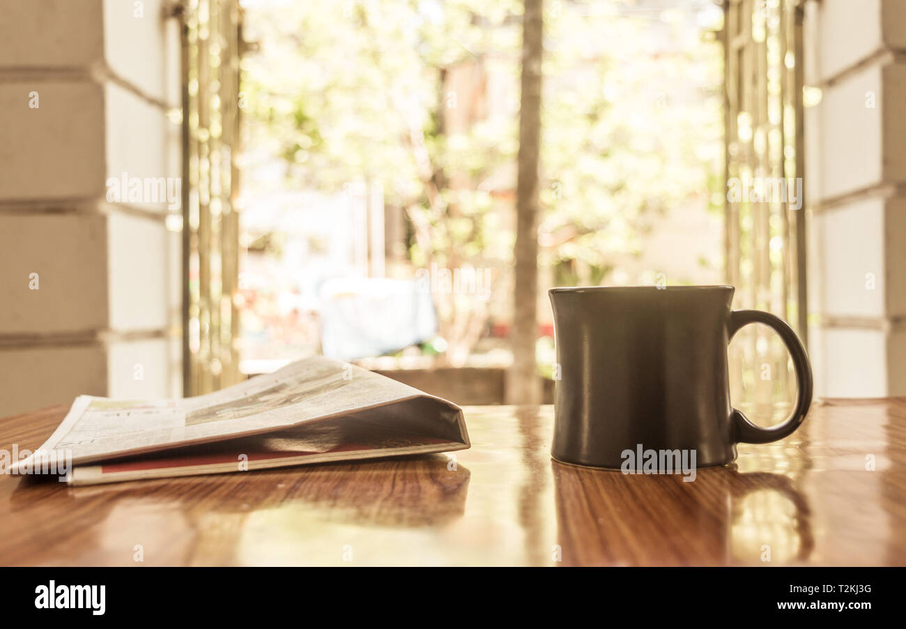Cappuccino aroma cup of coffee for breakfast in cafe on wooden table background with newspaper. Morning sunlight coming from window on sun day or holi - Stock Image