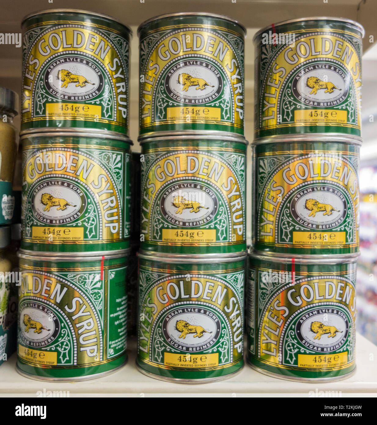 Tins of Lyle's Golden Syrup stacked on a supermarket shelf in London, UK - Stock Image