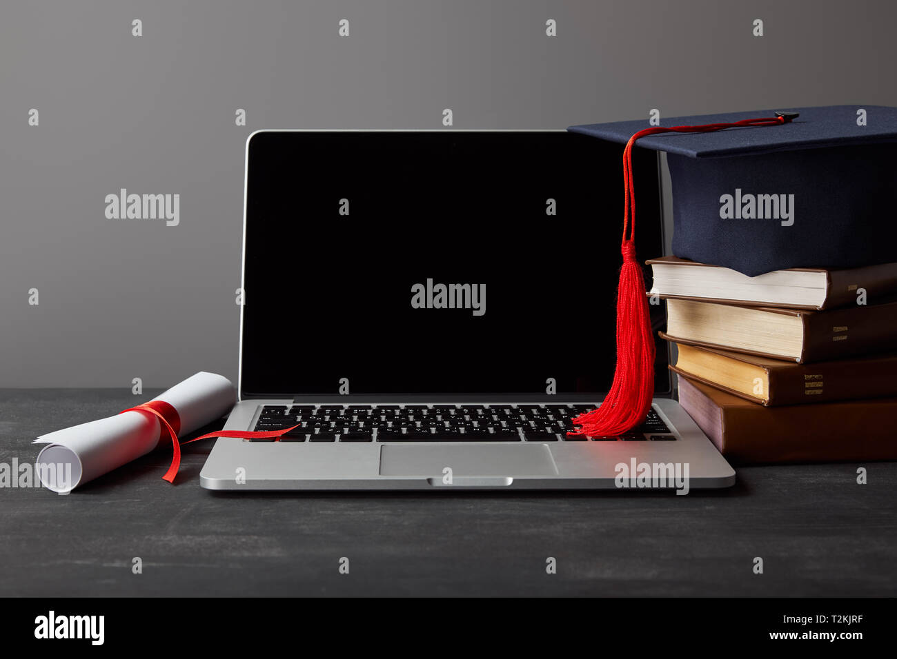 Laptop with blank screen, diploma, books and academic cap with red tassel isolated on grey - Stock Image