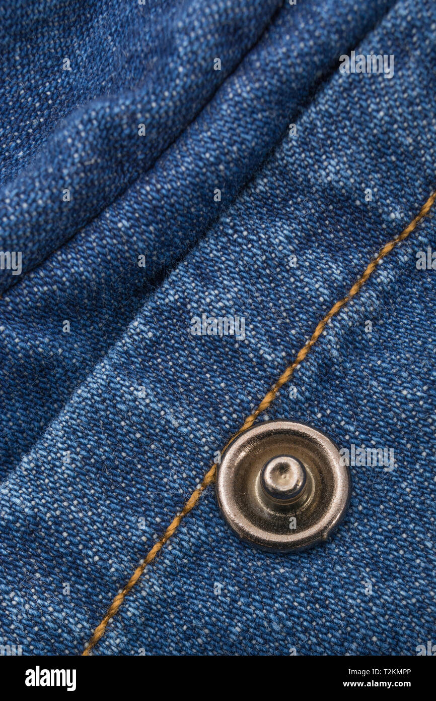 Close-up of blue denim fabric, showing warp and weft pattern thread pattern and orange stitching. - Stock Image