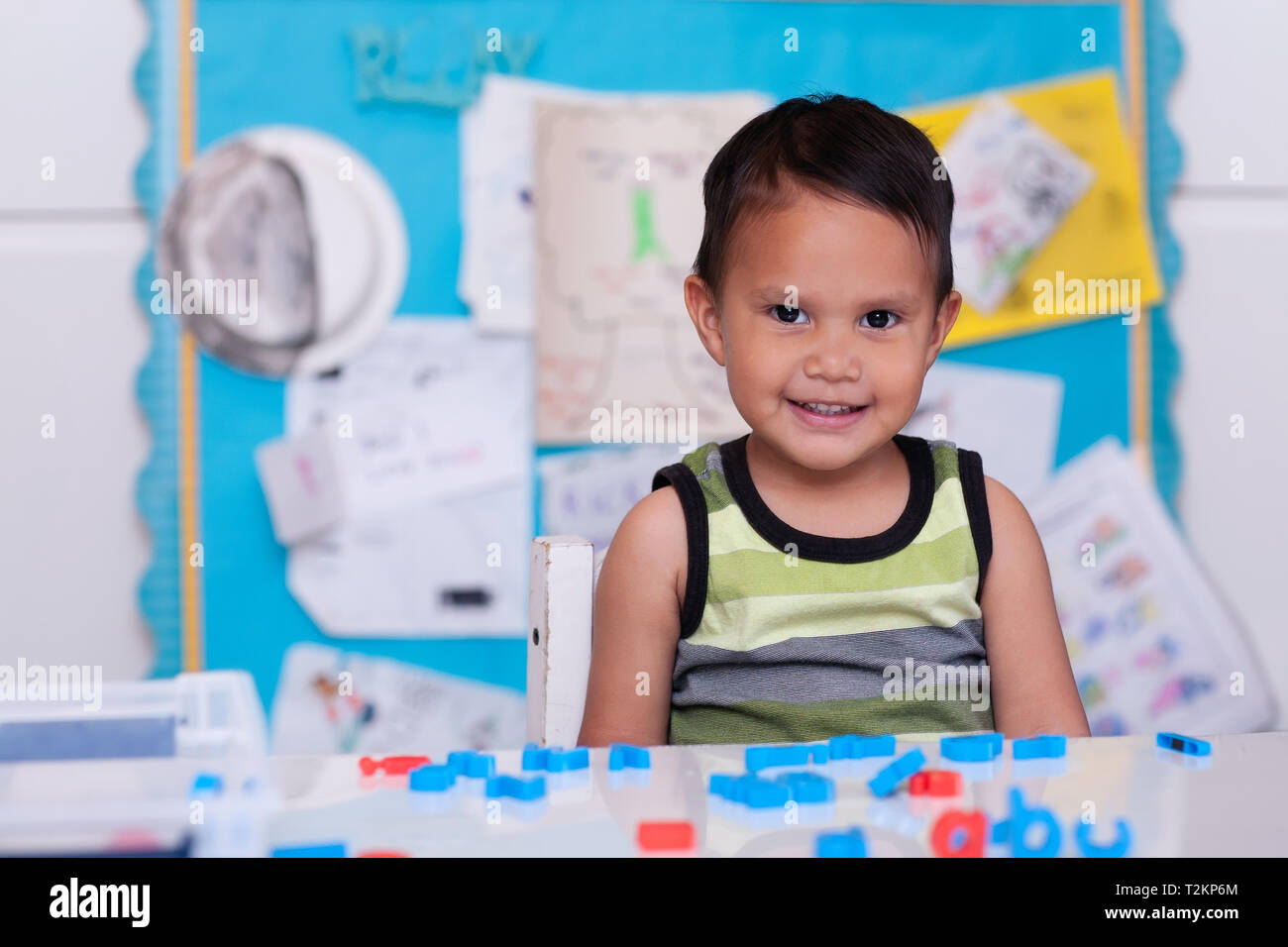 A cute Hispanic boy sitting in daycare with alphabet letters on the table and a colorful bulletin board in the background. Stock Photo