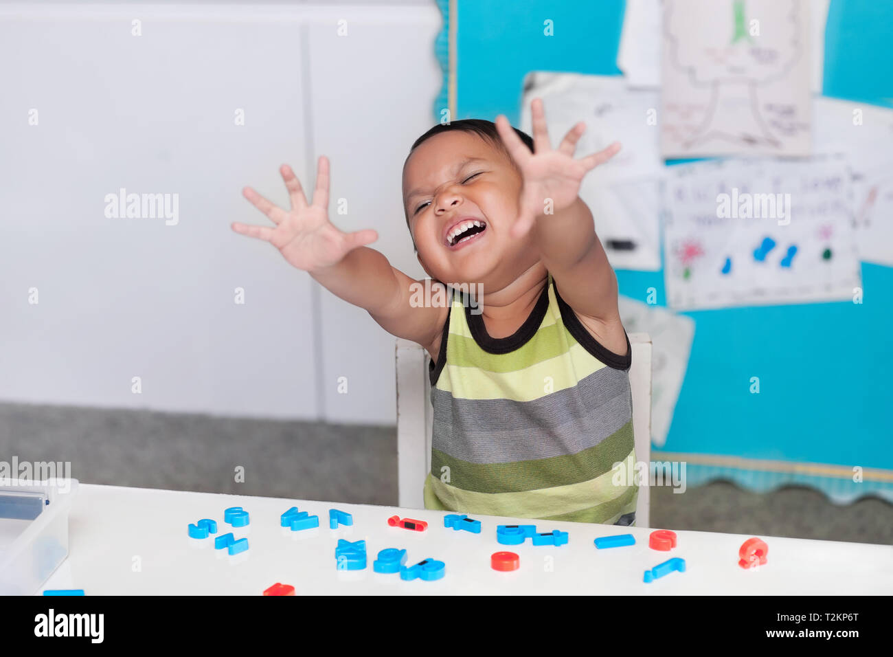 Hispanic young boy expressing disruptive or disorderly behavior in a classroom with alphabet letter manipulatives on the desk. - Stock Image