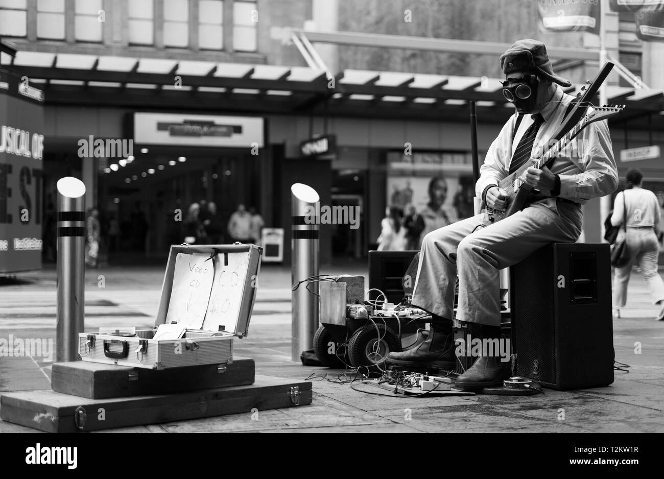 Street busker playing guitar with a gas mask on - Stock Image