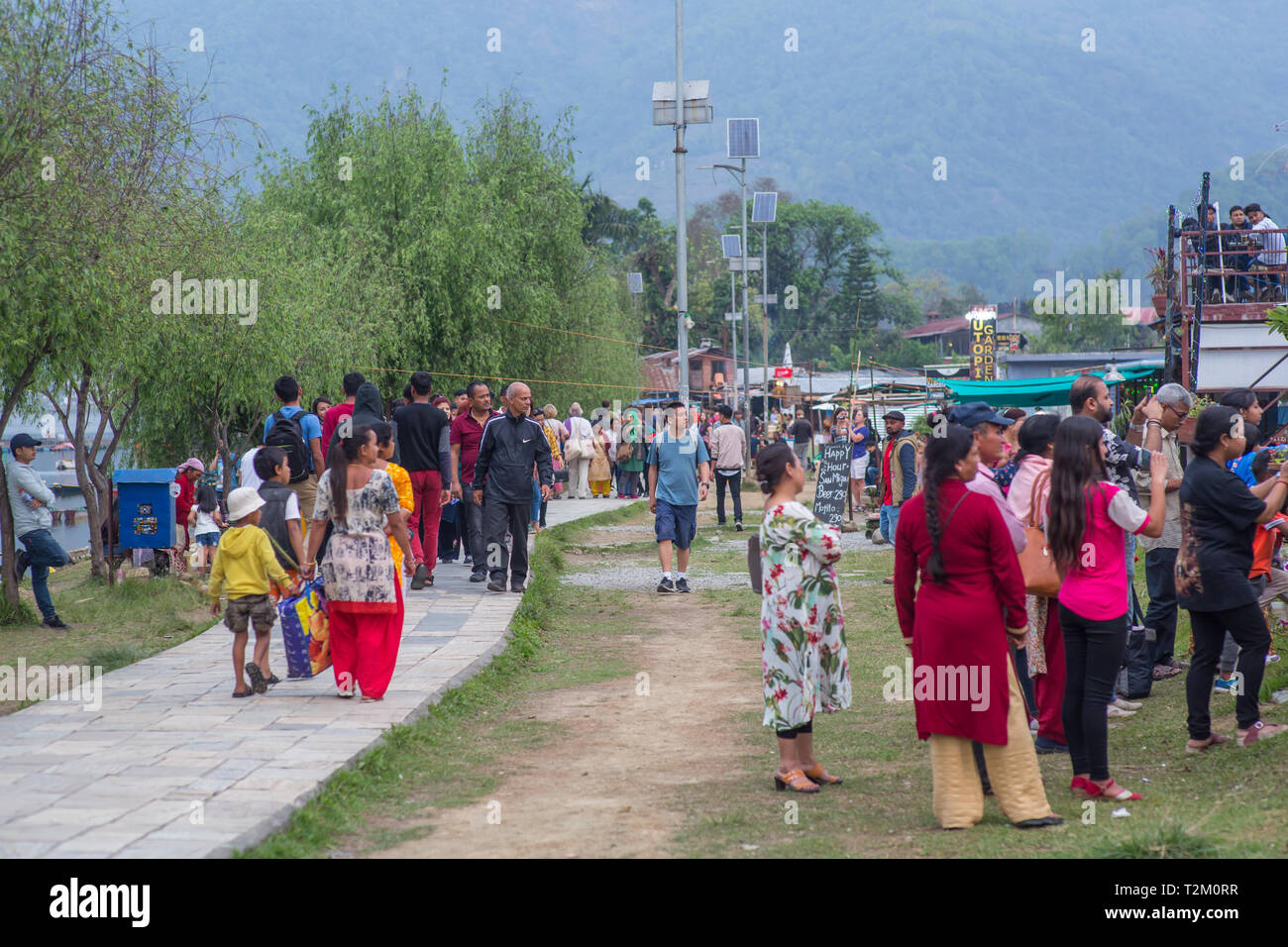 People walking along the lake in Pokhara, Nepal, on a foggy afternoon - Stock Image