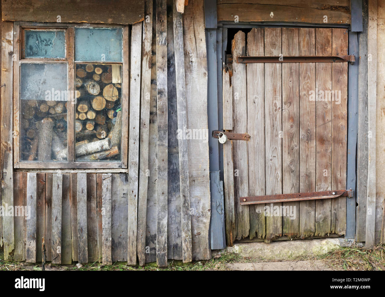 Usual no name wooden vintage  wall of rural shed for storage of firewood and agricultural tools. Panoramic collage from several outdoor shots - Stock Image