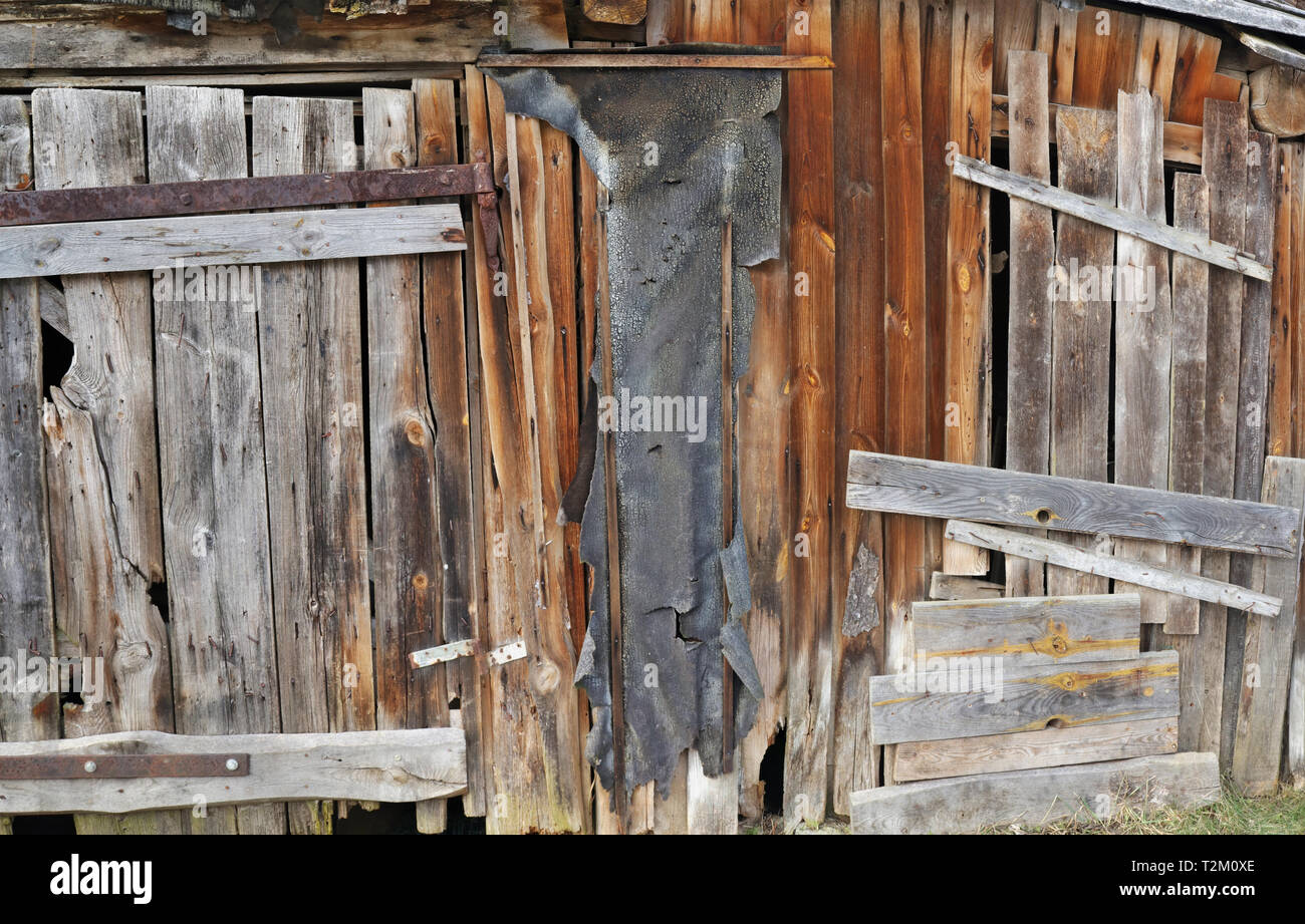Usual rotten curved  wooden vintage  wall of rural shed for storage of firewood and agricultural tools. Panoramic collage from several outdoor shots - Stock Image