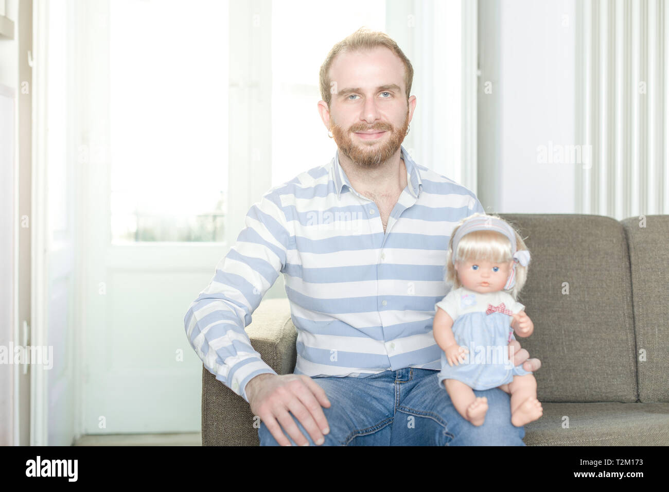 Smiling Redhead Man on a Couch with a Doll Sitting on His Knee - Stock Image