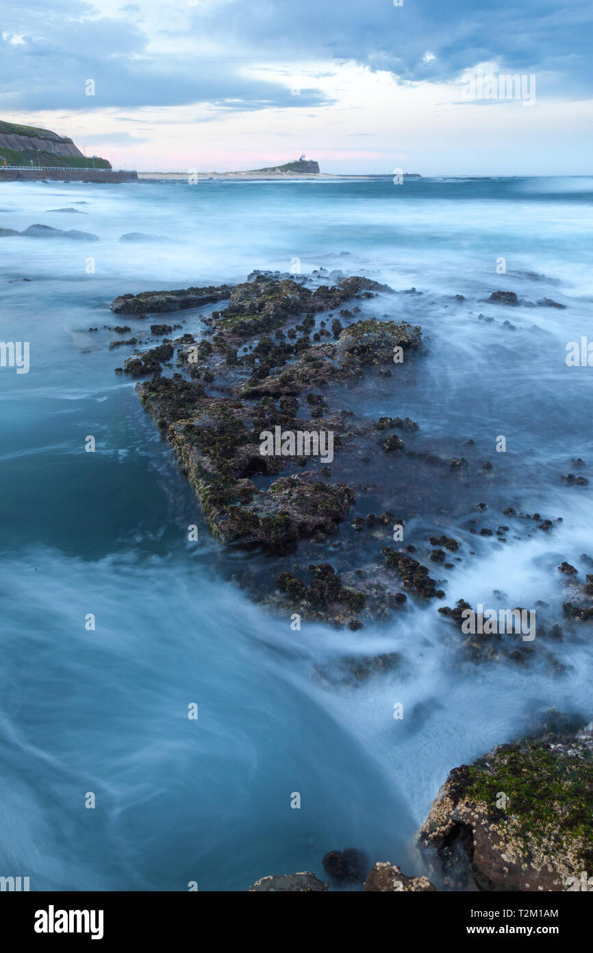 Rugged coastline towards Nobbys Lighthouse at Newcastle Ocean Baths - Newcastle Australia. Newcastle is New South Wales second largest city with some  - Stock Image