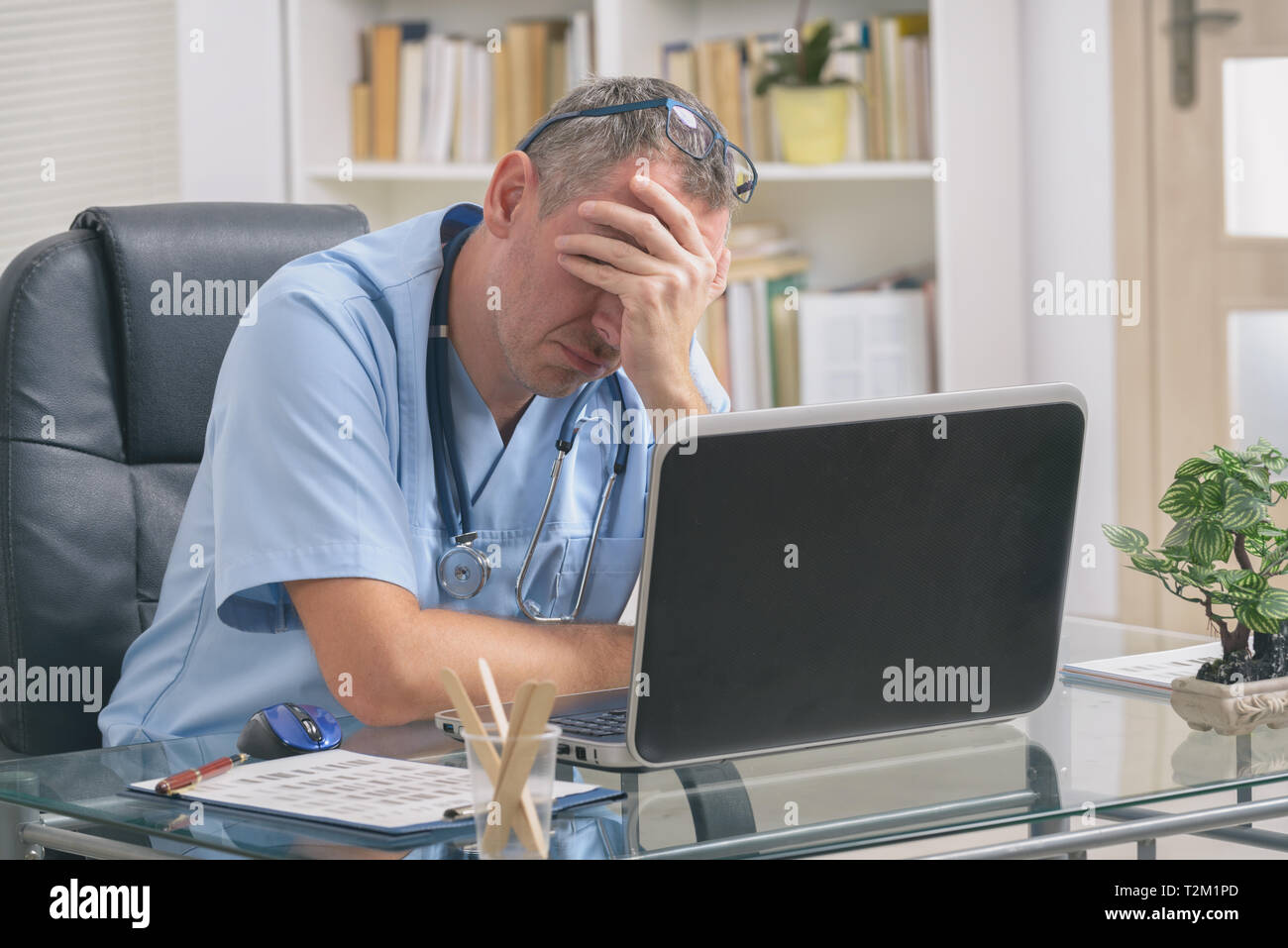 Overworked doctor sitting in his office - Stock Image