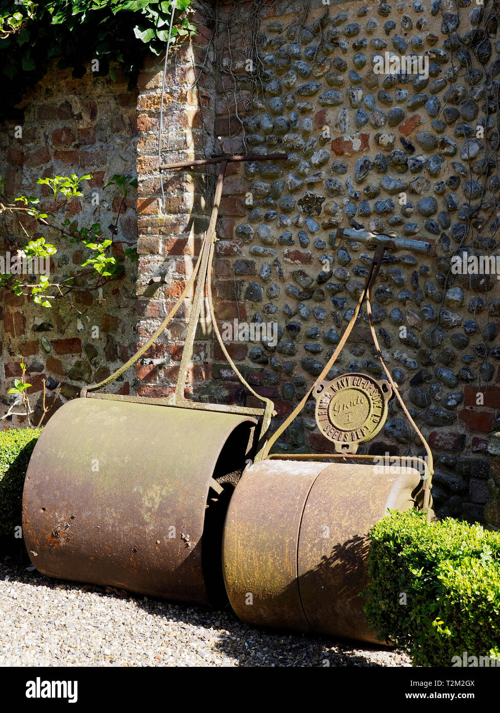 Two large possibly Victorian cast iron garden rollers leaning against abrick and flint garden wall. Stock Photo