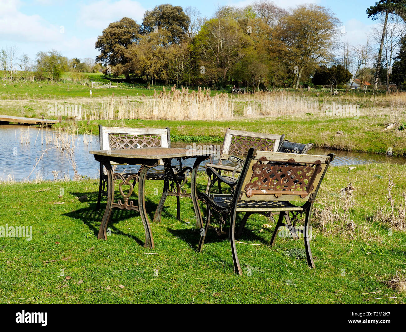 Heavy cast iron and wood garden furniture in a slightly surreal location in the middle of an area of meadow and man-made ponds. Stock Photo