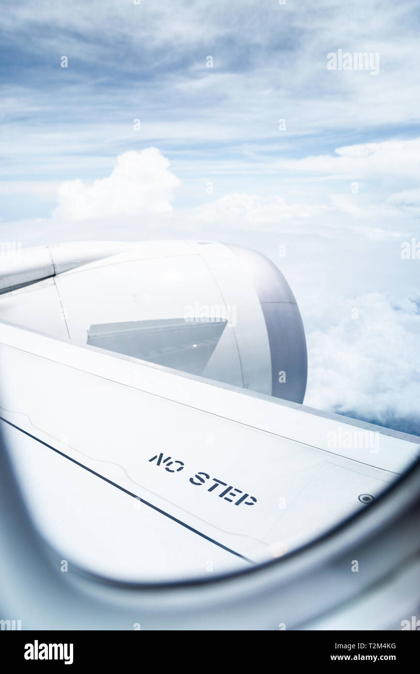 No step sign on commercial airplane wing, airplane in flight, shot through the window. Stock Photo