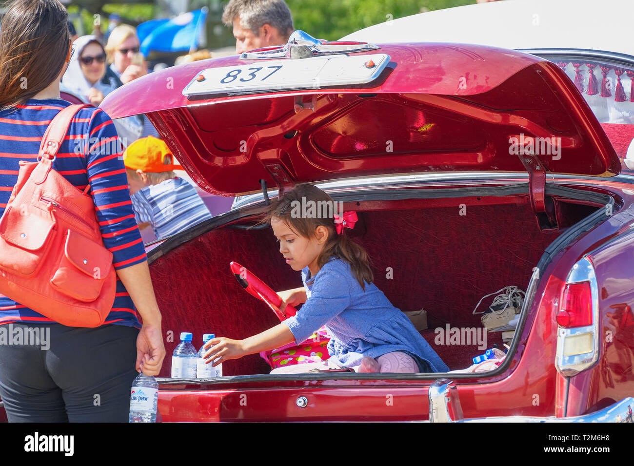 Samara, Russia - August 18, 2018: Girl plays sitting in the trunk of a car - Stock Image