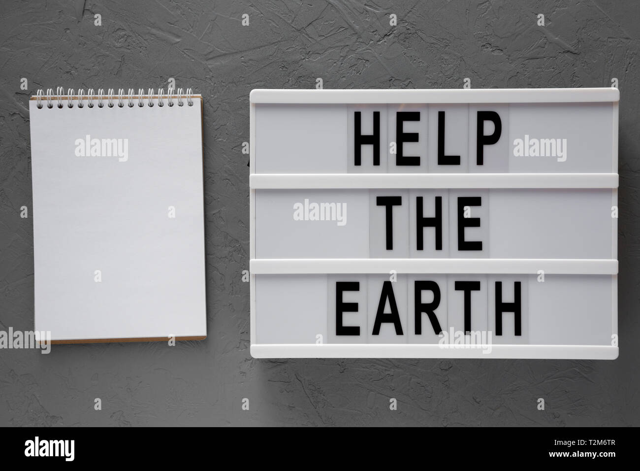 Help the Earth' words on modern board, blank notepad over