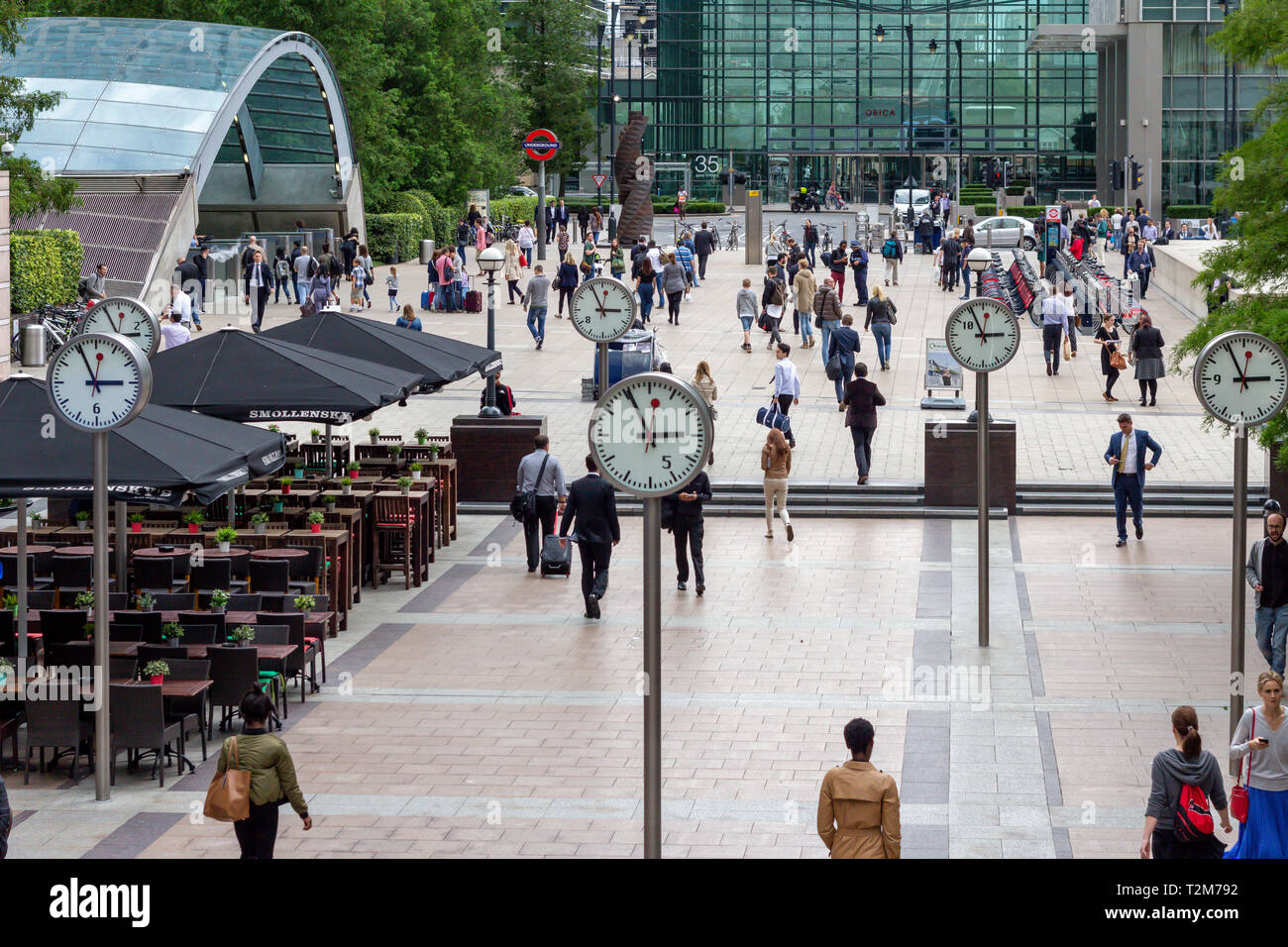 LONDON, ENGLAND - AUGUST 27 2015: Commuters walking through Reuters Plaza, Canary Wharf, London past the 'Six Public Clocks' by Konstantin Grcic - Stock Image