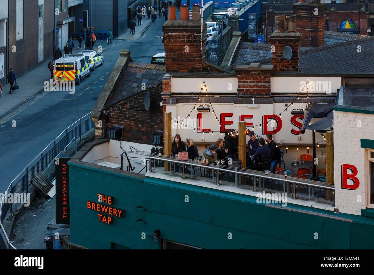 People sitting outside on roof terrace bar Leeds - Stock Image