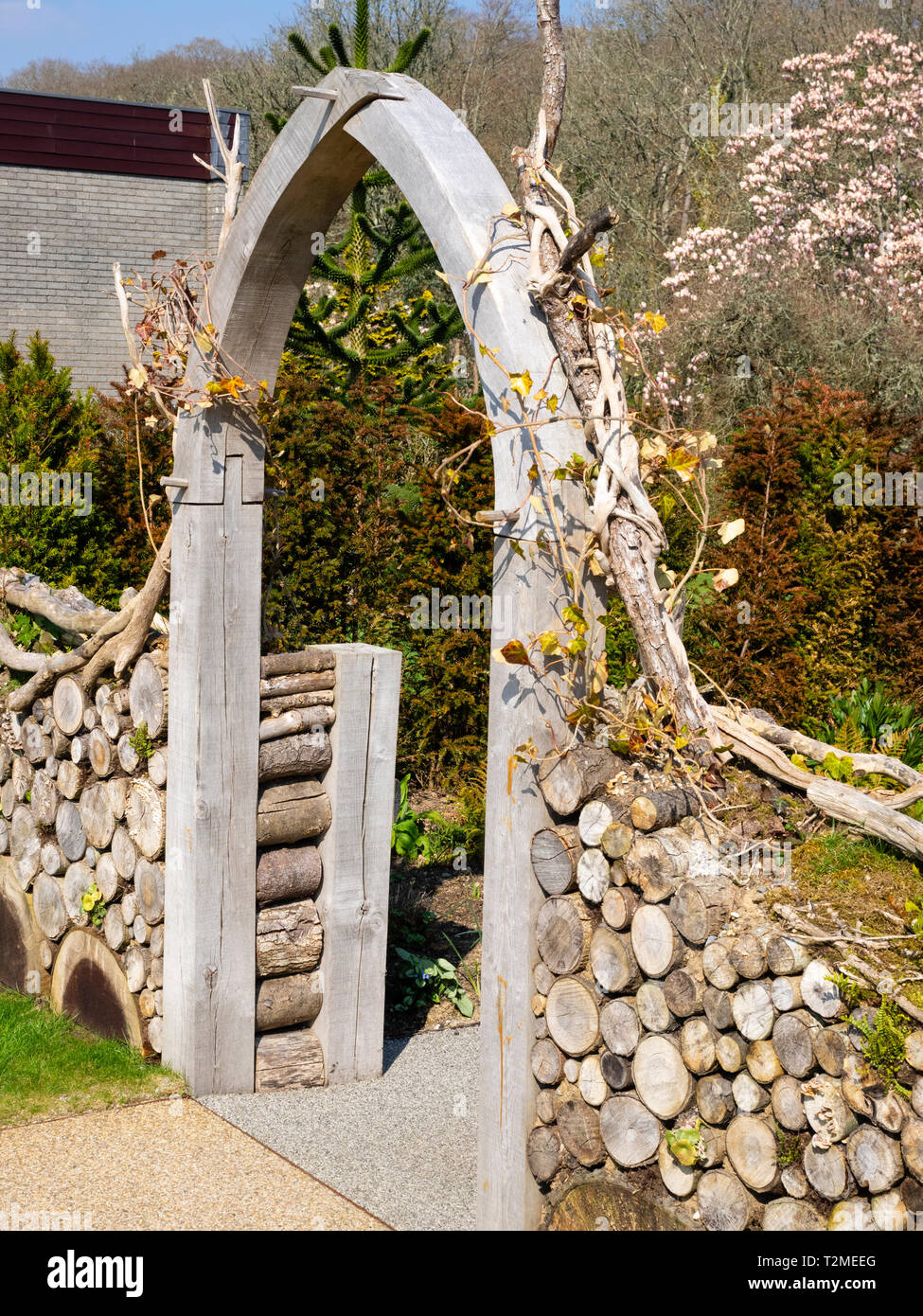 Cut log wall and green oak archway on the front of the Millenium Garden at Buckfast Abbey, Devon, UK - Stock Image