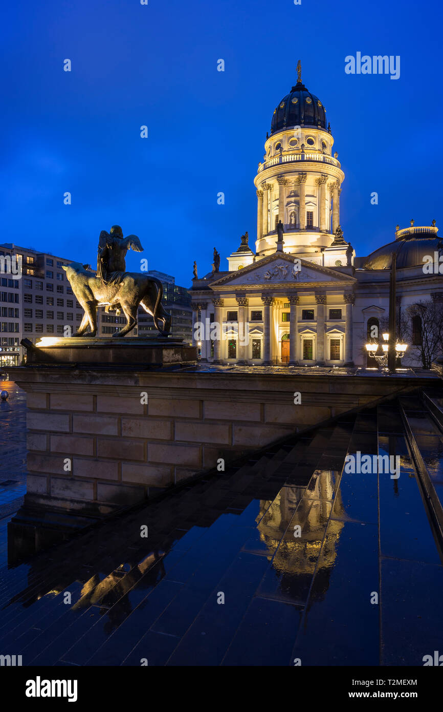 Lit Neue Kirche (Deutscher Dom, German Church or German Cathedral) and a statue in front of the Konzerthaus Berlin at Gendarmenmarkt Square at dusk. Stock Photo
