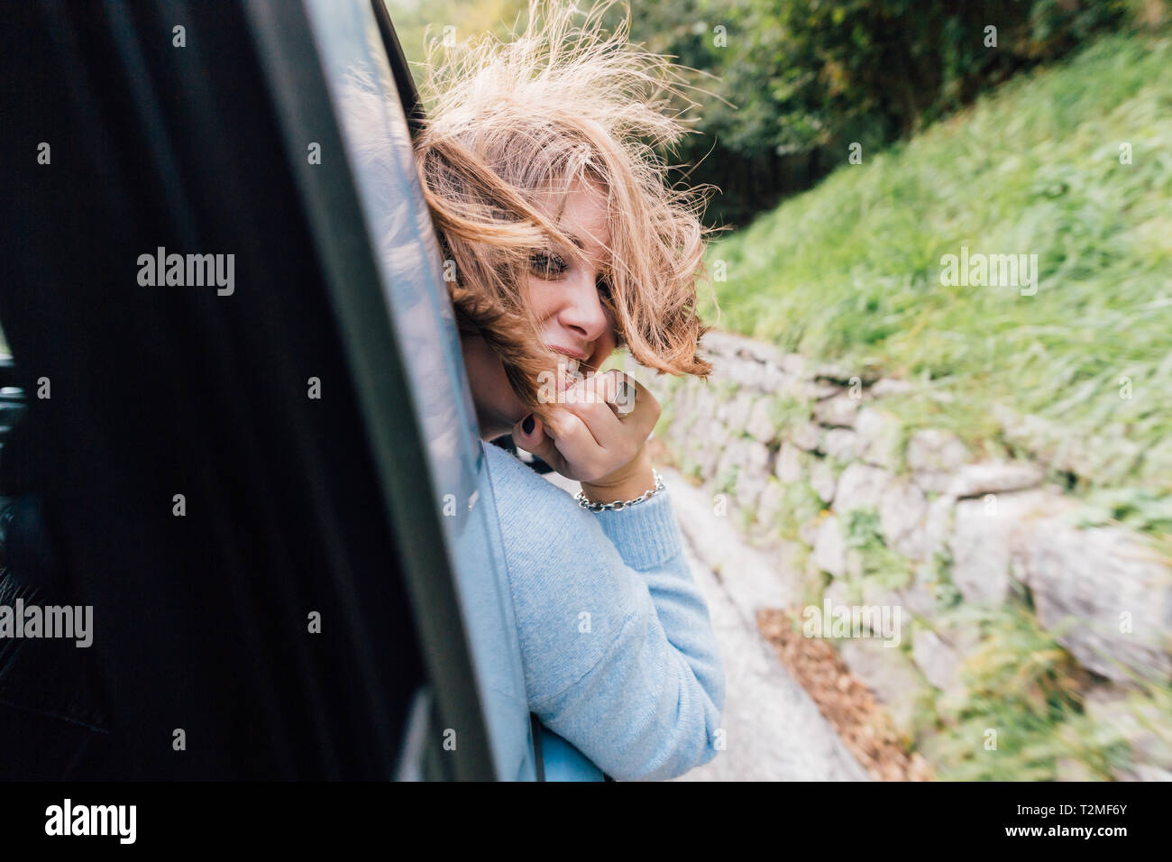 Woman turning around out of car window Stock Photo
