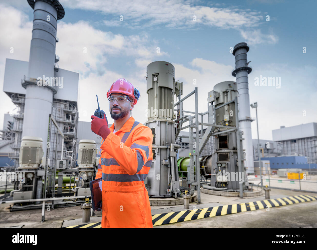 Composite image of worker using walkie talkie in powerstation - Stock Image