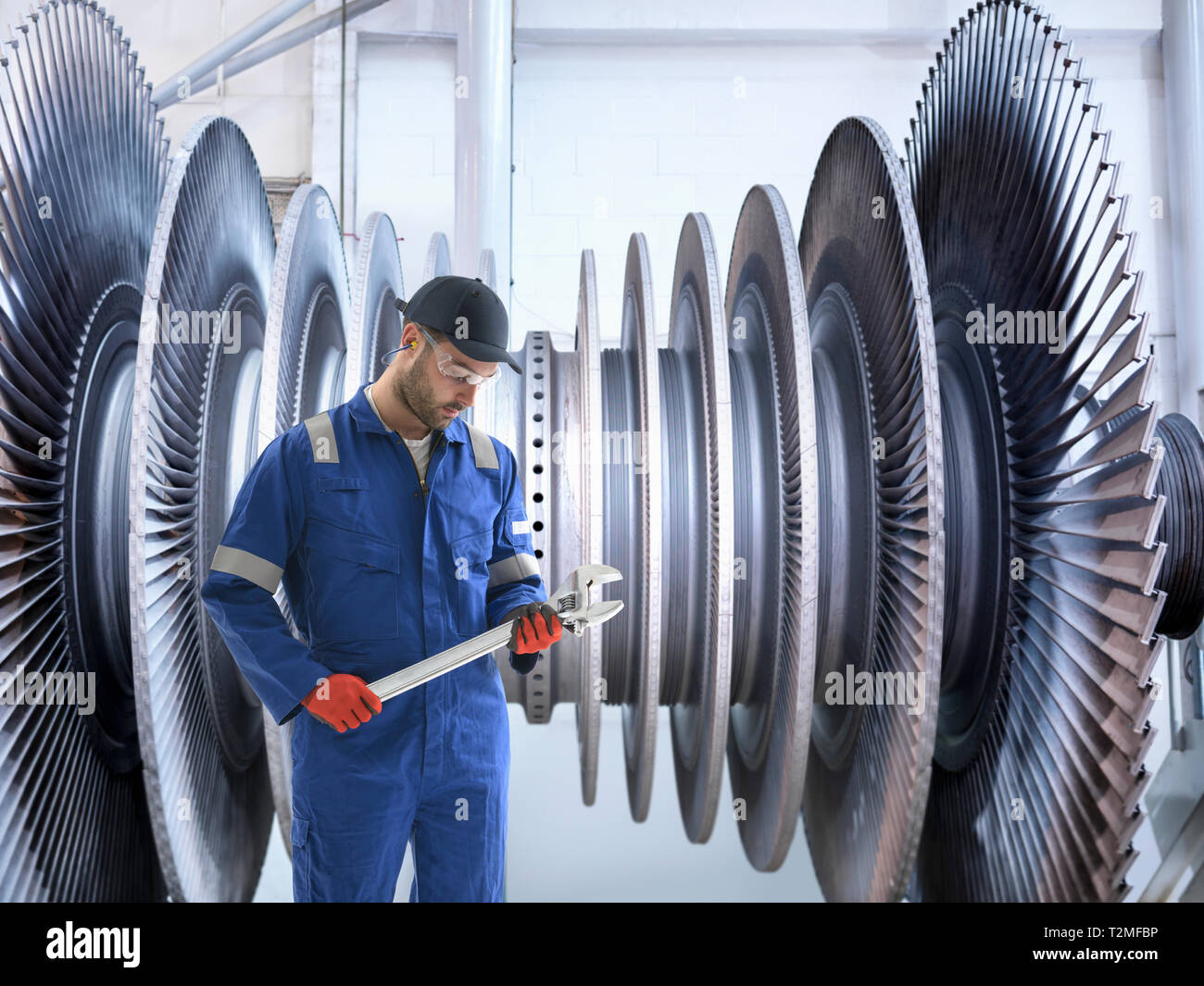Composite image of engineer with turbine blades in power station workshop - Stock Image
