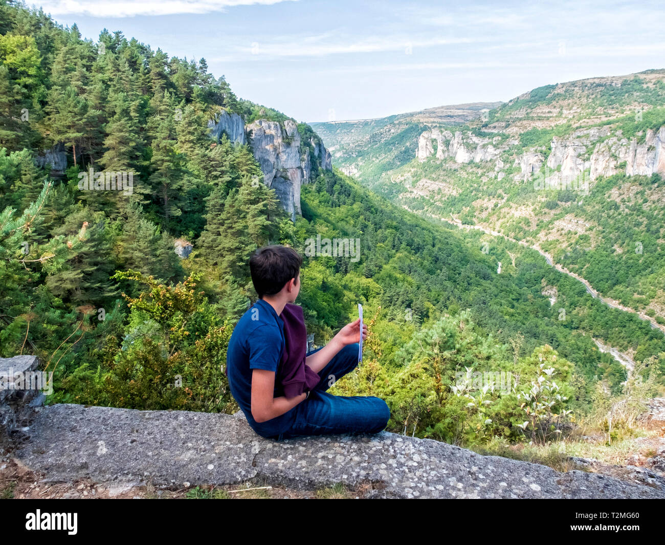 Rear view of a boy sitting on a rock formation and looking at the view - Stock Image