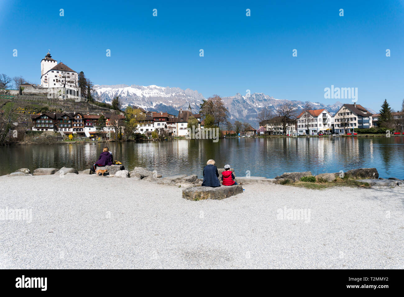 Werdenberg, SG / Switzerland - March 31, 2019: tourists enjoy a visit to idyllic and historic Werdenberg village and lake with a great view of the Swi - Stock Image