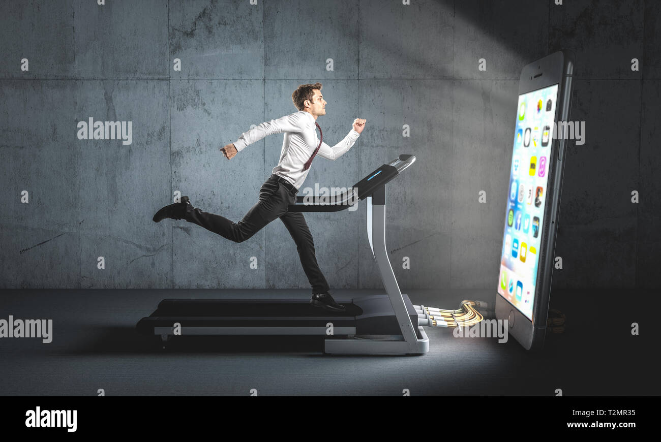 Businessman runs on a treadmill to feed a big smartphone he can't do without. Concept of attachment to technology and dependence. - Stock Image