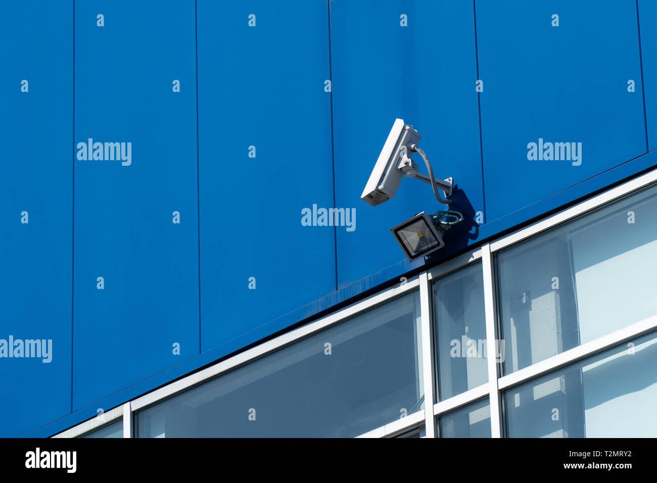 Surveillance concept. Security camera on blue building facade - Stock Image