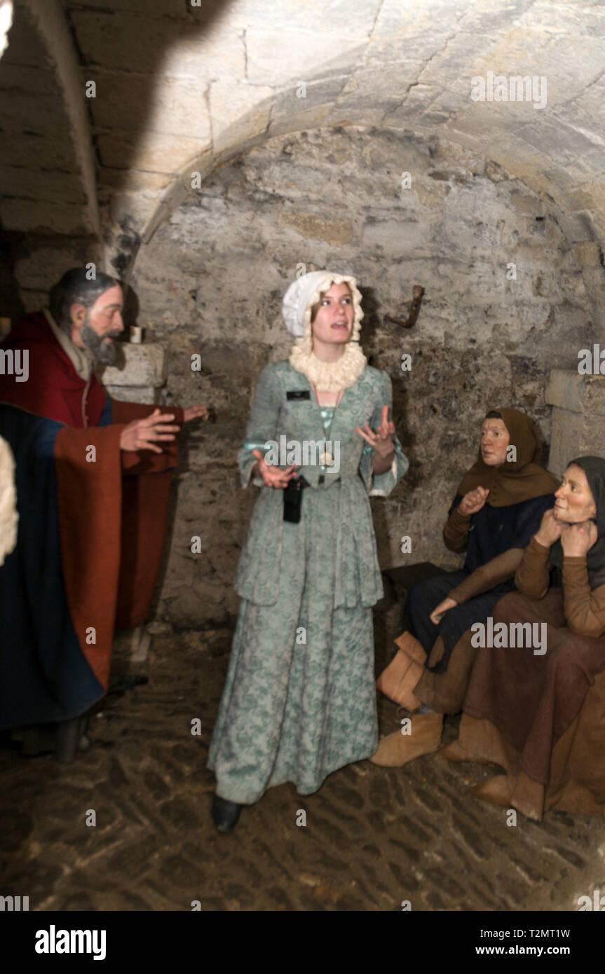 A tour guide dressed as a female prisoner, Mary Bandy in the 900 year old underground crypt at Oxford Castle & Prison in Oxford, Britain.   The guide  - Stock Image