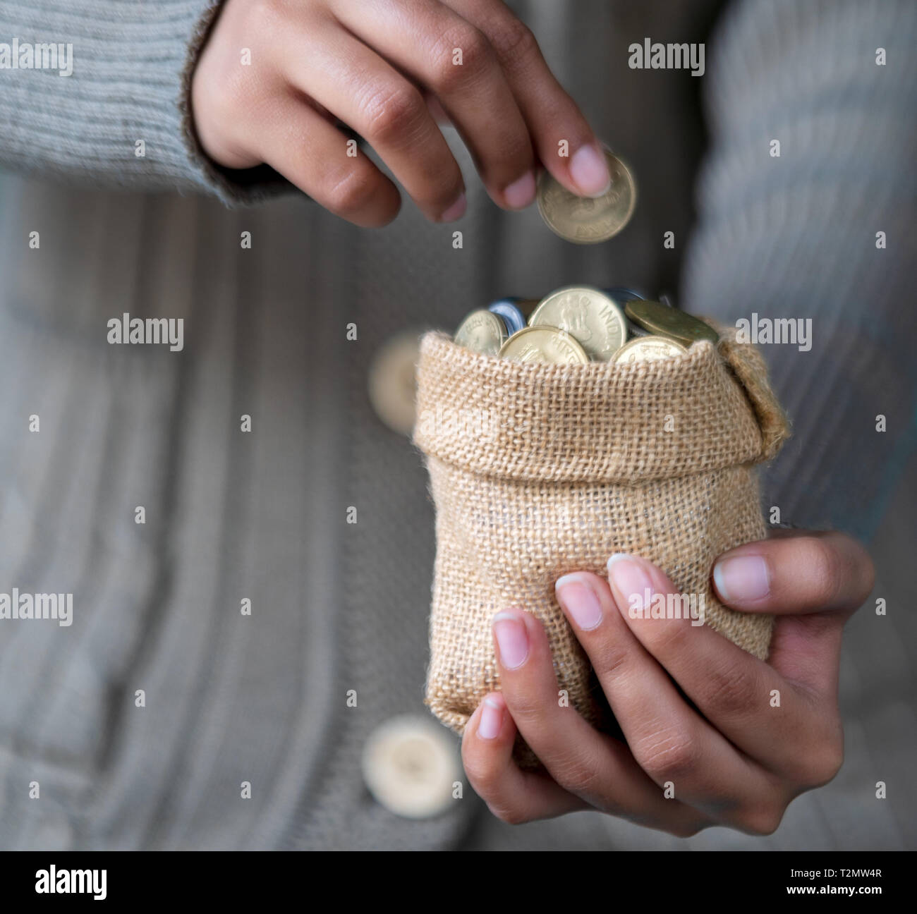 Saving money or coins in a sack holding in a young female hand for brighter future education. - Stock Image