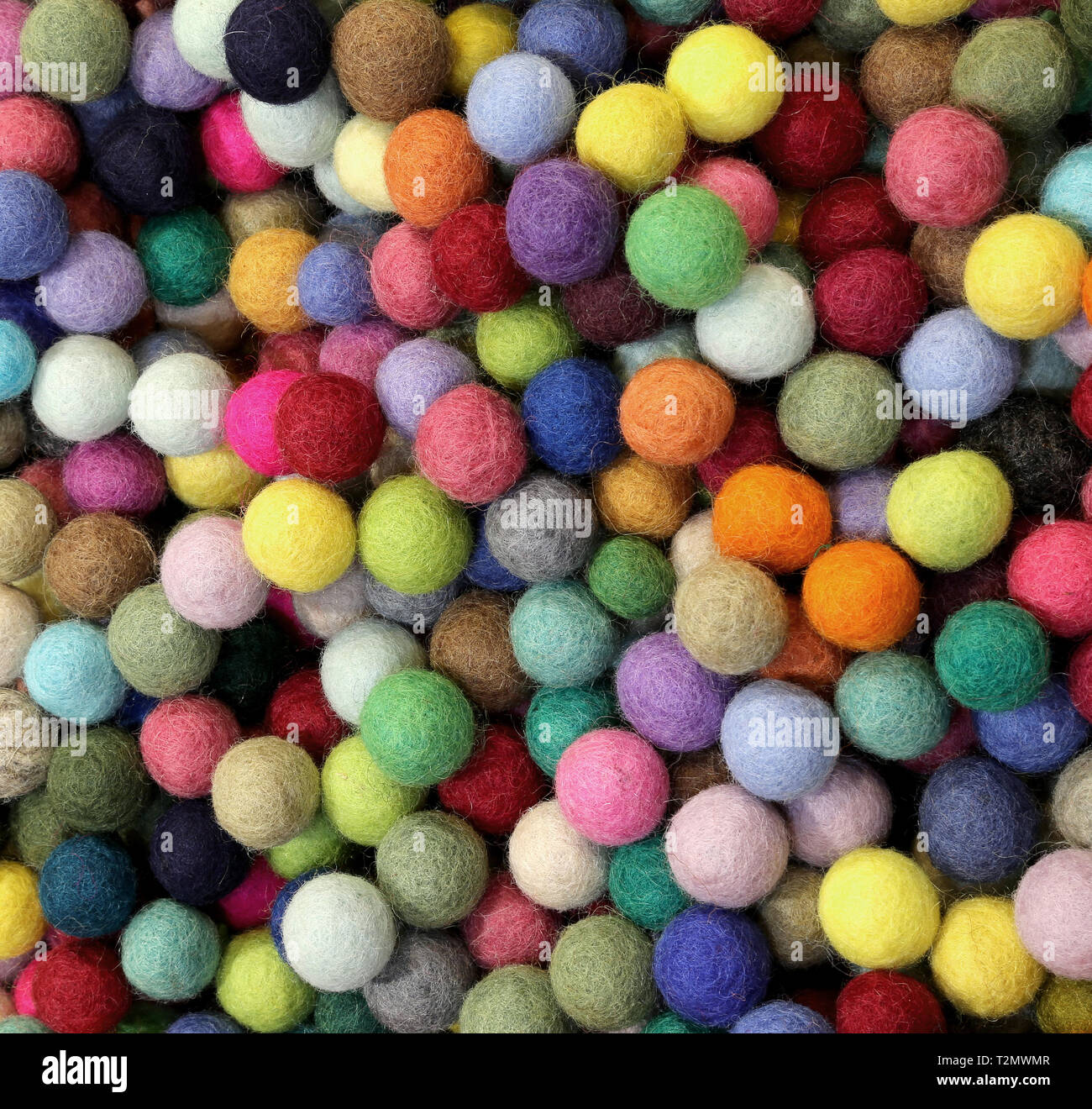 background of many multicolored felt small balls - Stock Image