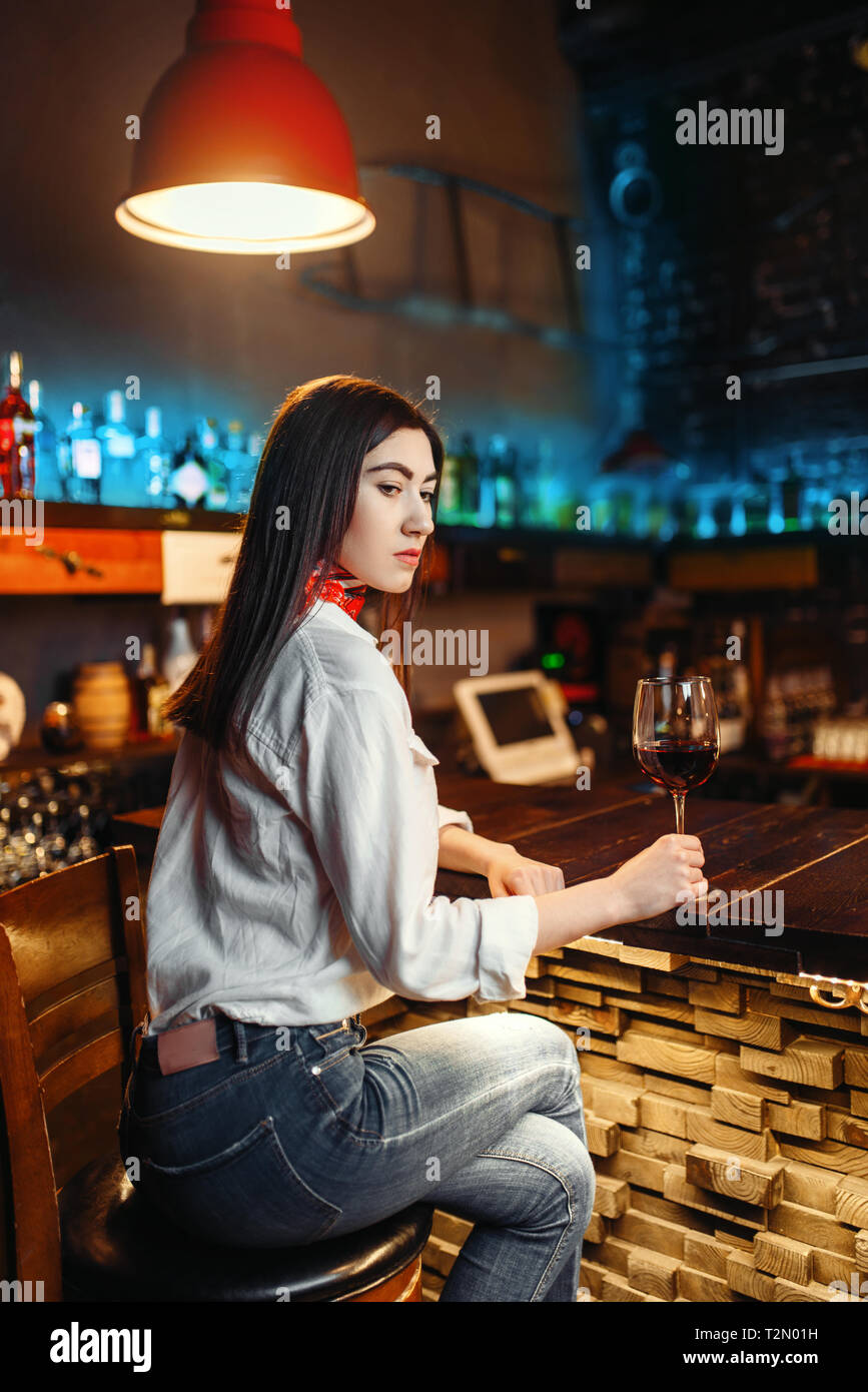 Young lady with glass of red wine sitting at wooden bar counter. Female customer leisures in pub - Stock Image