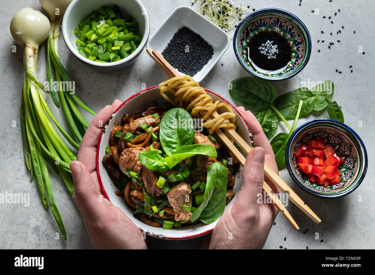Hands holding bowl withc chinese udon noodles and beef, vegatables on the gray table.  Top view Stock Photo
