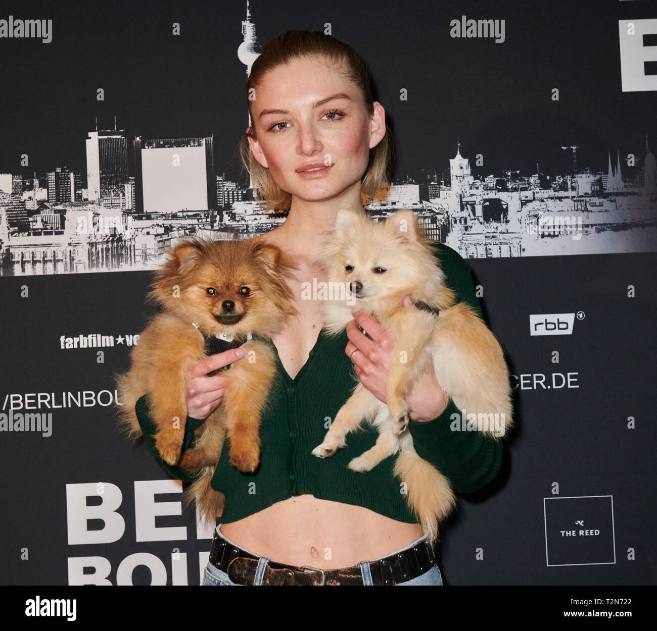 Berlin, Germany. 03rd Apr, 2019. Ex-GNTM candidate Julia Wulf stands with her dogs Wilson and Amy in front of the photo wall for the cinema premiere Berlin Bouncer. Credit: Annette Riedl/dpa/Alamy Live News - Stock Image