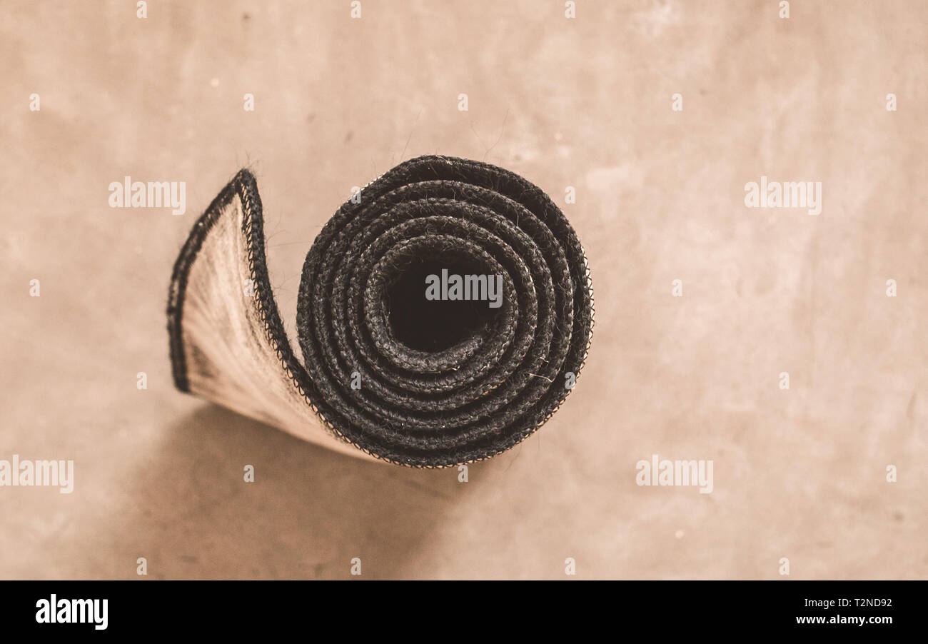 Rolled yoga mat after exercise isolated on rustic cement floor background in a sport activity center. Fitness, Healthy life, keep fit, lifestyle welln - Stock Image