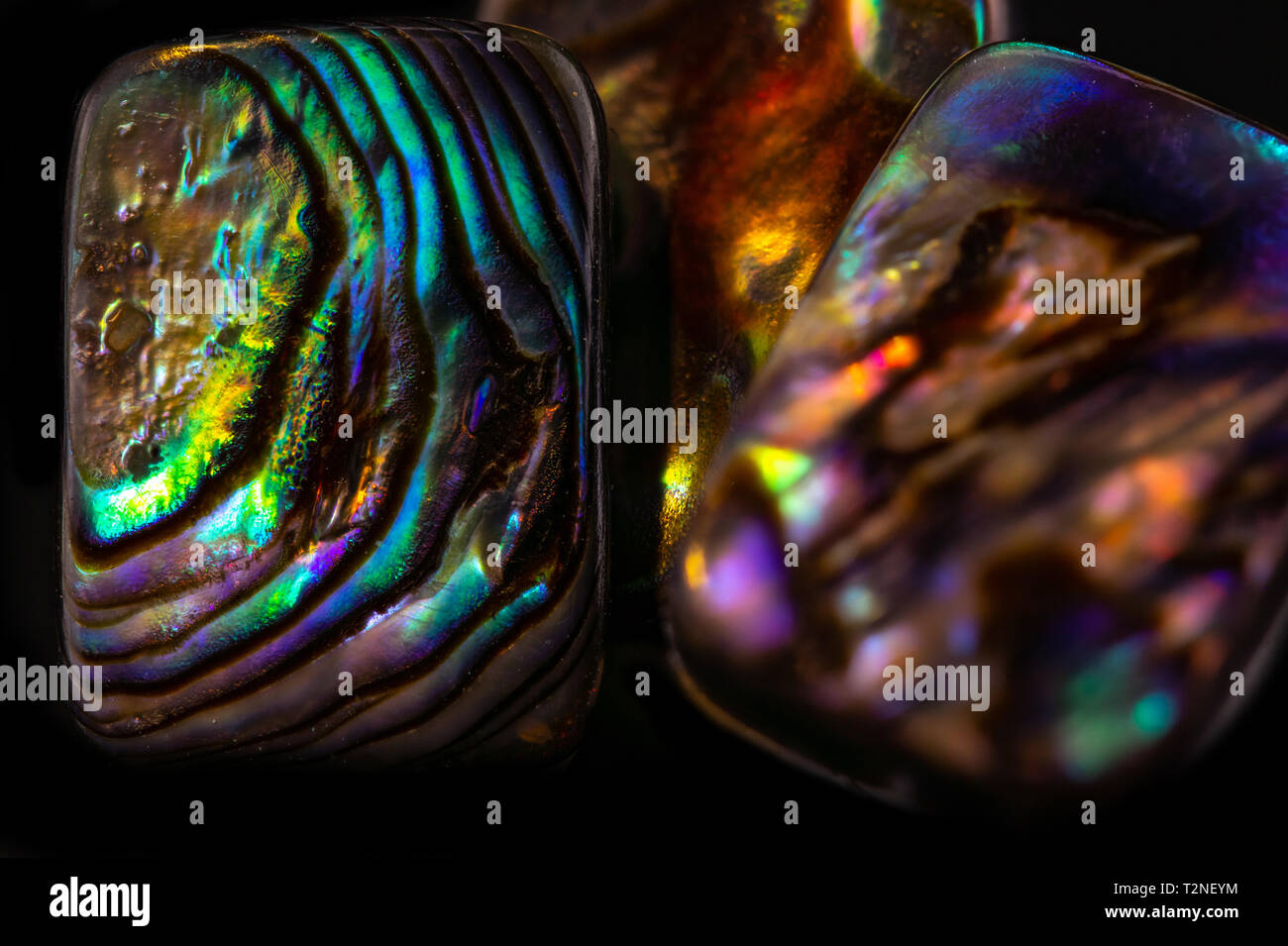 abstract gemstone background, colorful nacre shimmering on black background - Stock Image
