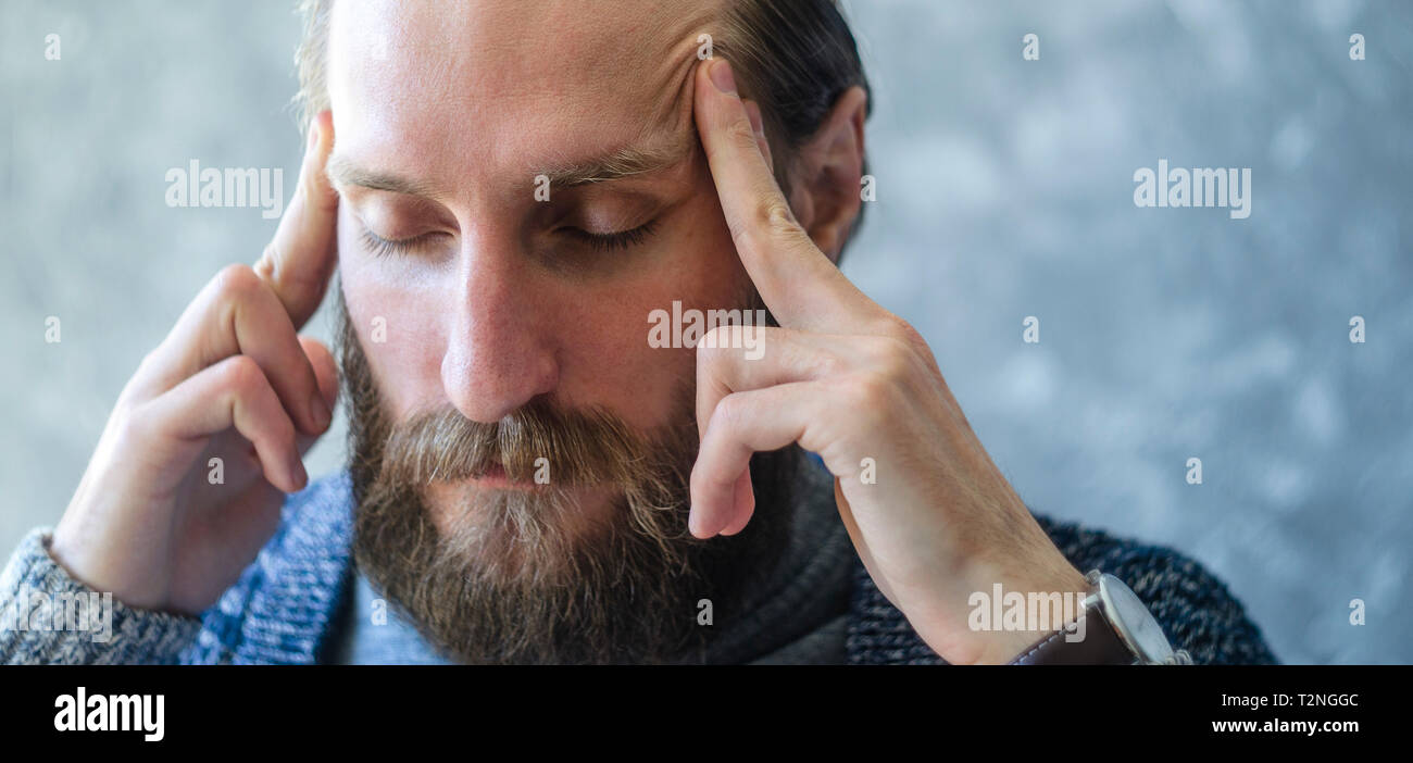 A Tired Young Man with a Beard Massages His Temples with His Fingers. Pensive Meditative State Concept - Stock Image