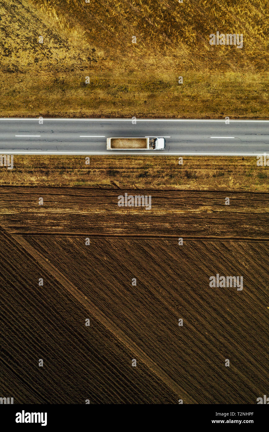 Truck on road, aerial view of freight transporter on straight roadway through plain countryside landscape from drone pov - Stock Image