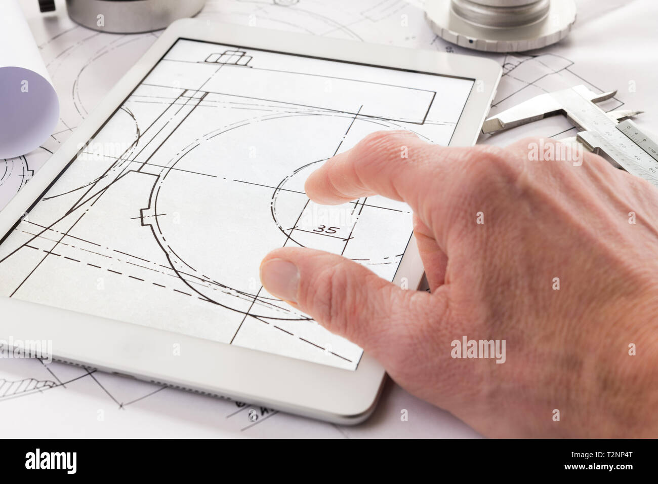 table with tablet computer, Technical drawing, caliper gauge, metal workpiece, Stock Photo