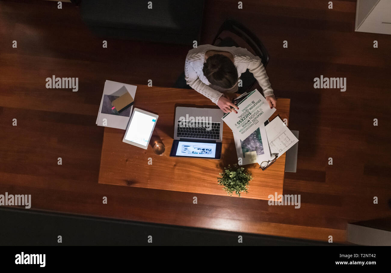 Woman working late at home Stock Photo