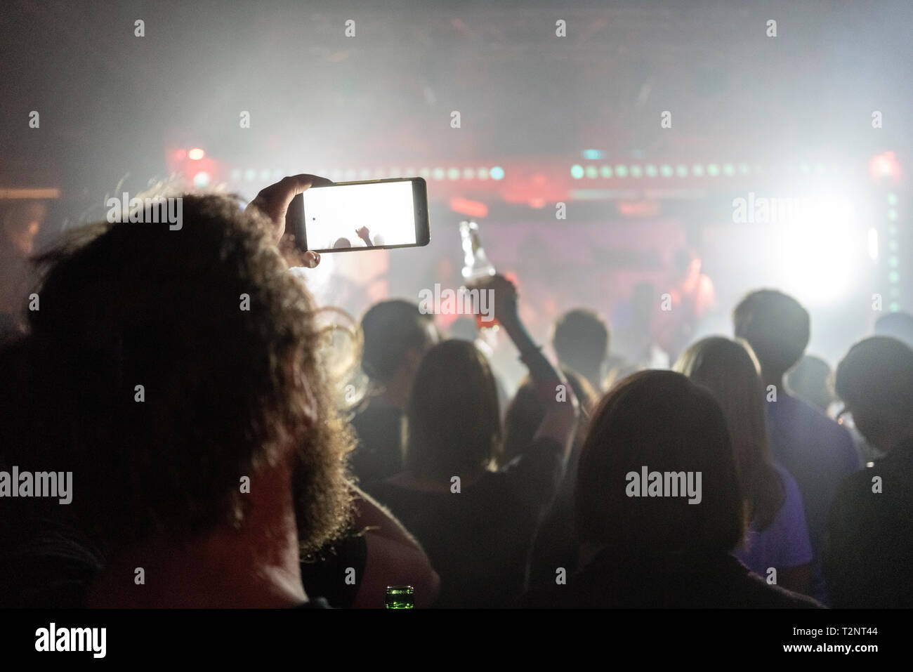 Man taking photograph of concert with smartphone - Stock Image