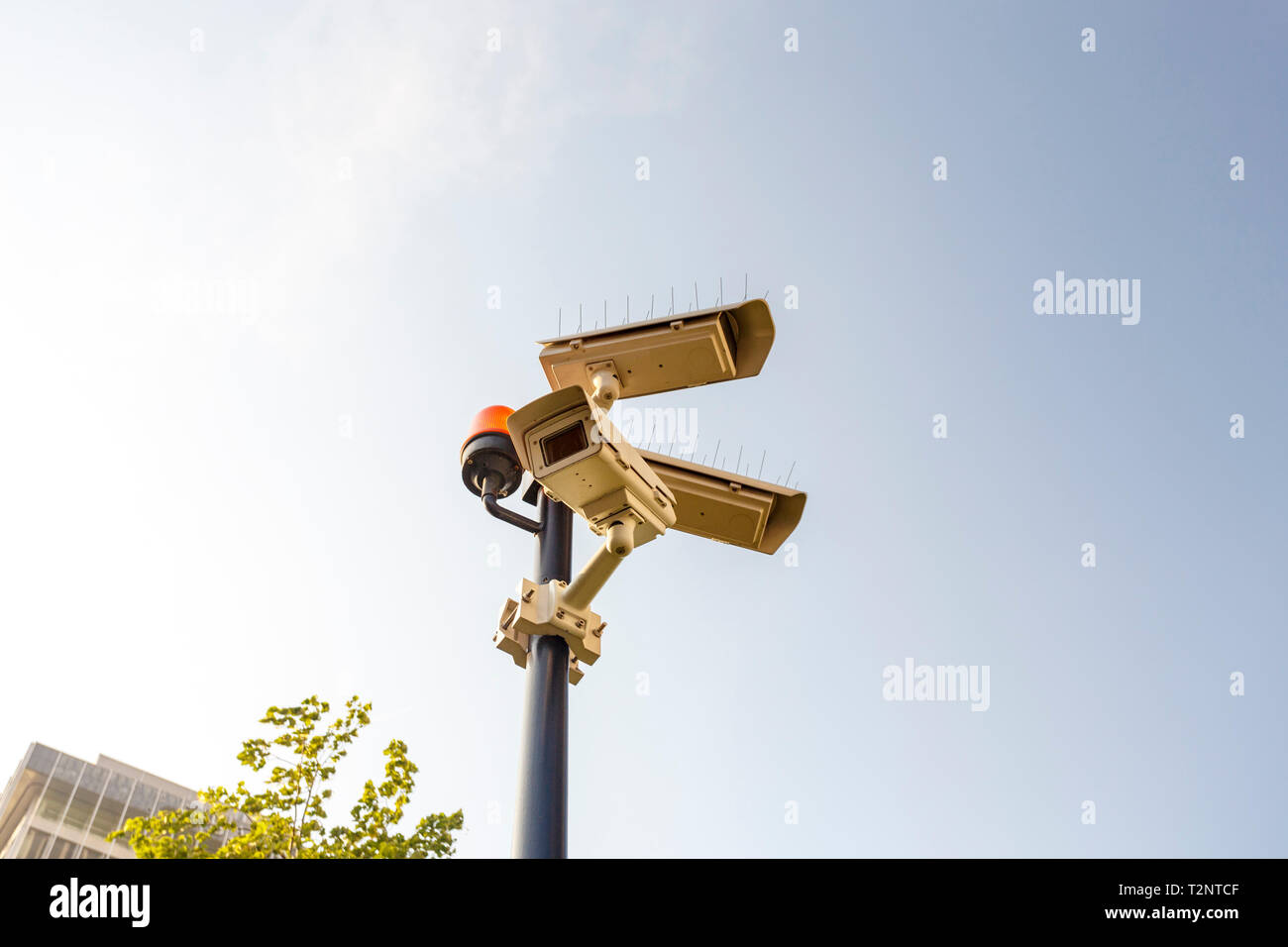 Surveillance camera against clear sunny sky - Stock Image