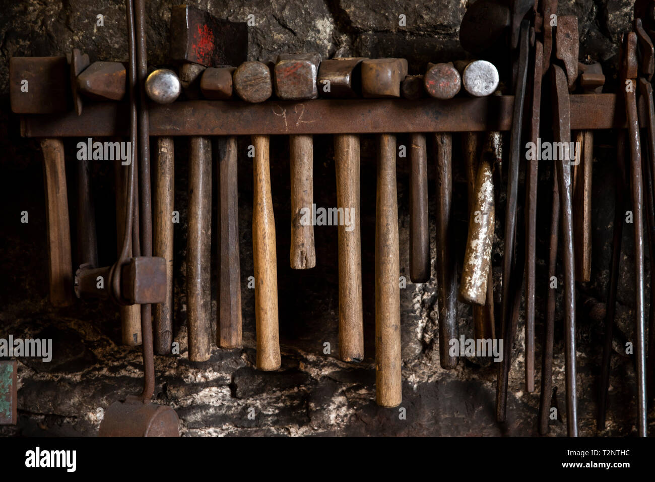 Row of blacksmiths hammers and tongs on workshop wall - Stock Image