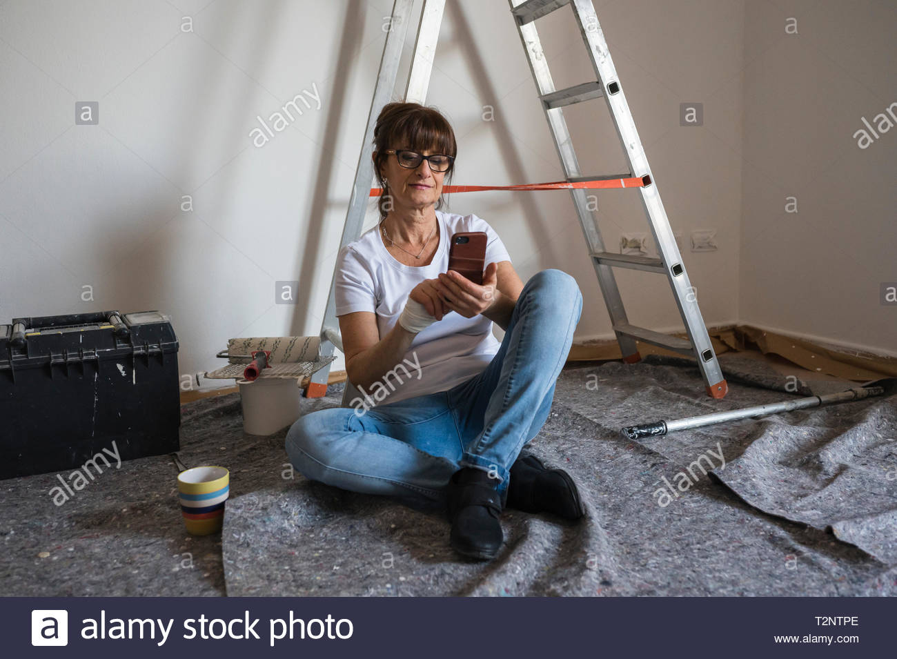 Senior woman decorating house interior sitting on floor looking at smartphone - Stock Image