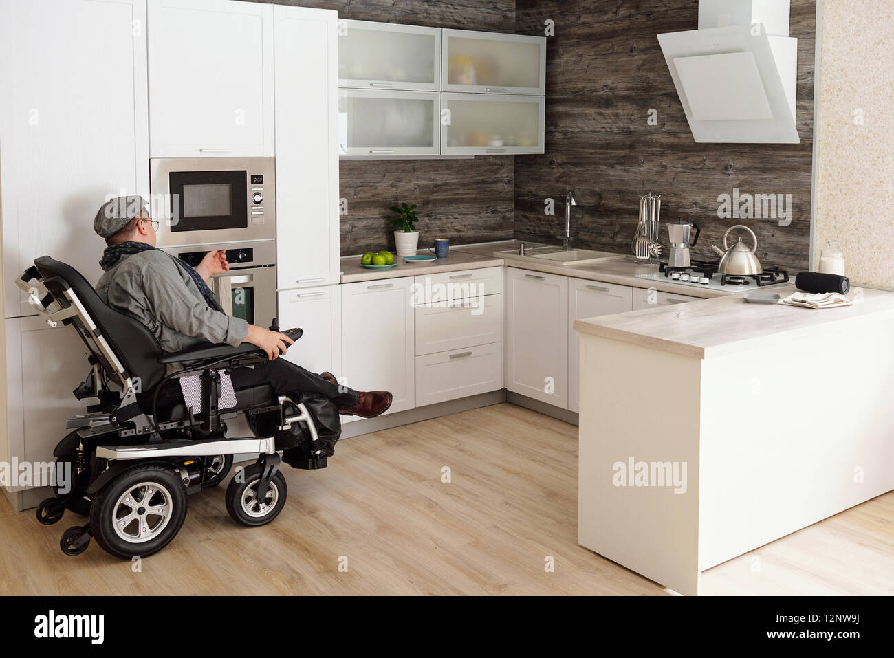 Physically impaired man switching on oven in kitchen Stock Photo